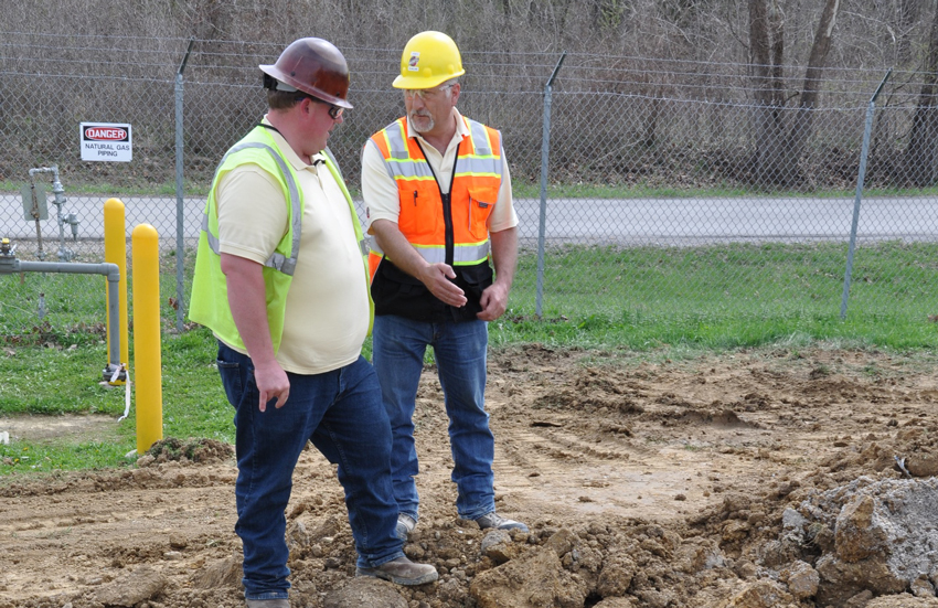 James Duncan, Explosive Destruction Technology (EDT) project safety specialist, top right, discusses a storm sewer excavation with Patrick Eidson, EDT civil superintendent.