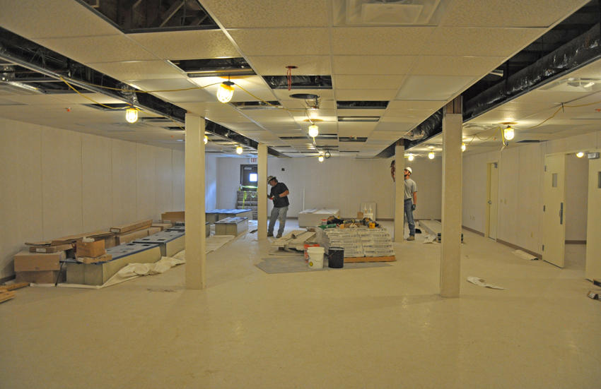 Workers finish columns in the cafeteria area of the Personnel Maintenance Building, where personnel will have lockers, showers and a break room while the project is in operations.
