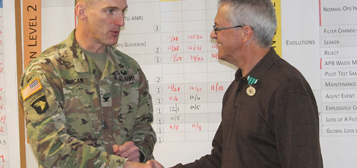 Bruce Huenefeld is congratulated by Col. Thomas Duncan, commander, Pueblo Chemical Depot after receiving the Distinguished Civilian Service Award Dec. 15. Huenefeld's last day on the job is Dec. 31.