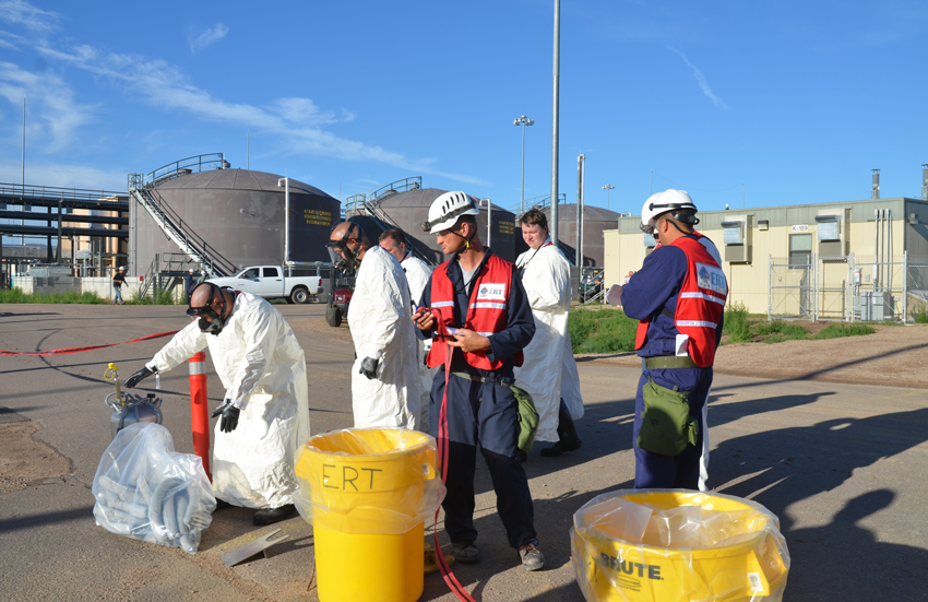 An evaluator watches as an Emergency Response Team performs an acid spill drill at the Pueblo plant. Drills are conducted routinely as a part of plant optimization.