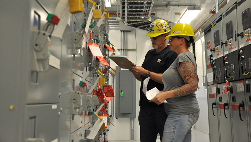Stephanie Jakus, instrumentation and electrical maintenance supervisor, right, inspects electrical equipment that has been locked out/tagged out to ensure no power is flowing through those circuits before anyone performs work on them.