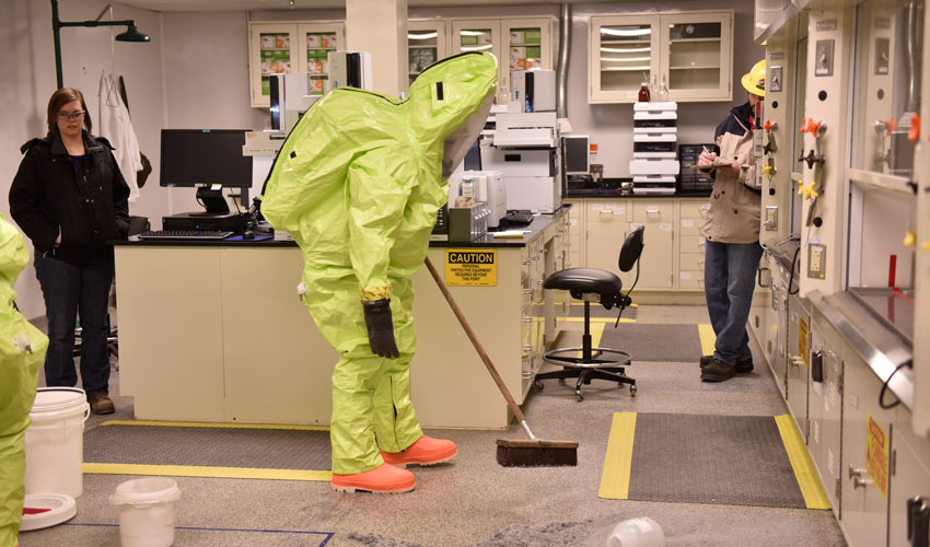 A Blue Grass Army Depot firefighter cleans up a simulated hydrolysate spill at the Blue Grass Chemical Agent-Destruction Pilot Plant Laboratory as observers evaluate the activity Jan. 31.