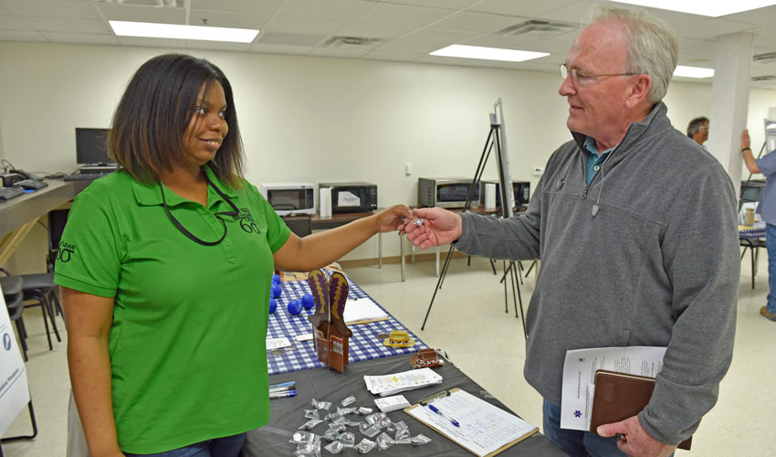A safety team member hands an employee a pin reflecting a safety-culture belief at the first Blue Grass Chemical Agent-Destruction Pilot Plant safety fair.