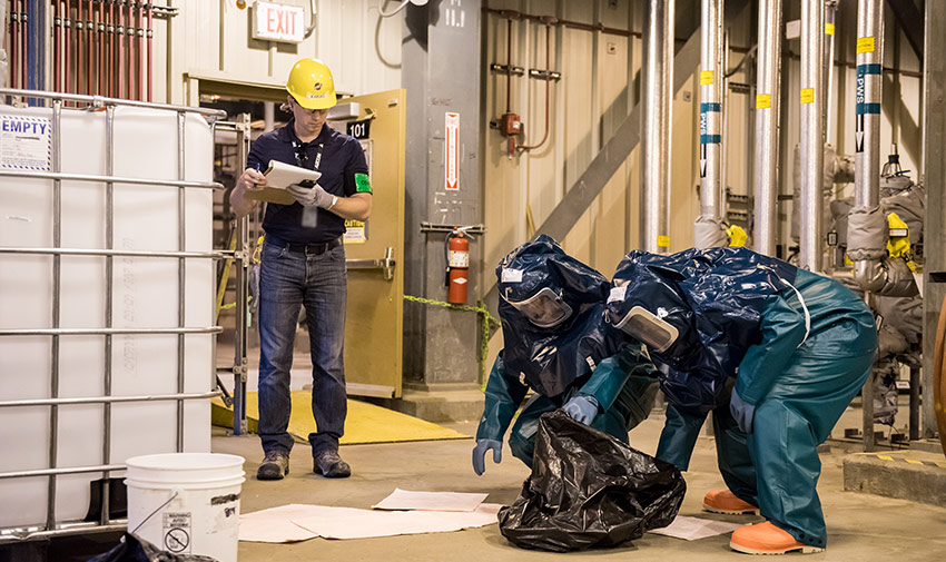 An evaluator watches as Blue Grass Chemical Agent-Destruction Pilot Plant technicians clean up a simulated caustic leak during an April drill.