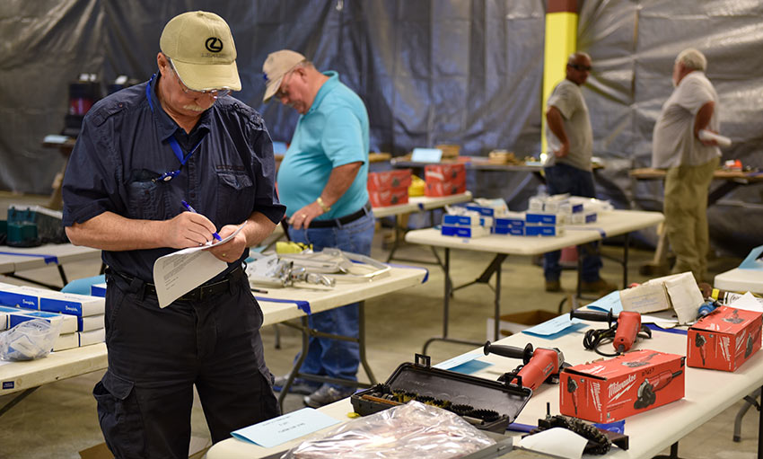 Community members look over items no longer needed by the Blue Grass Chemical Agent-Destruction Pilot Plant, such as new and used tools, at the May 31 public viewing for the project's first public auction of such items.