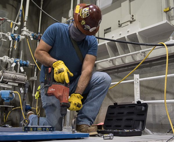 A worker drills holes in the concrete floor to install an equipment mounting plate in the Munitions Demilitarization Building at the Blue Grass Chemical Agent-Destruction Pilot Plant.