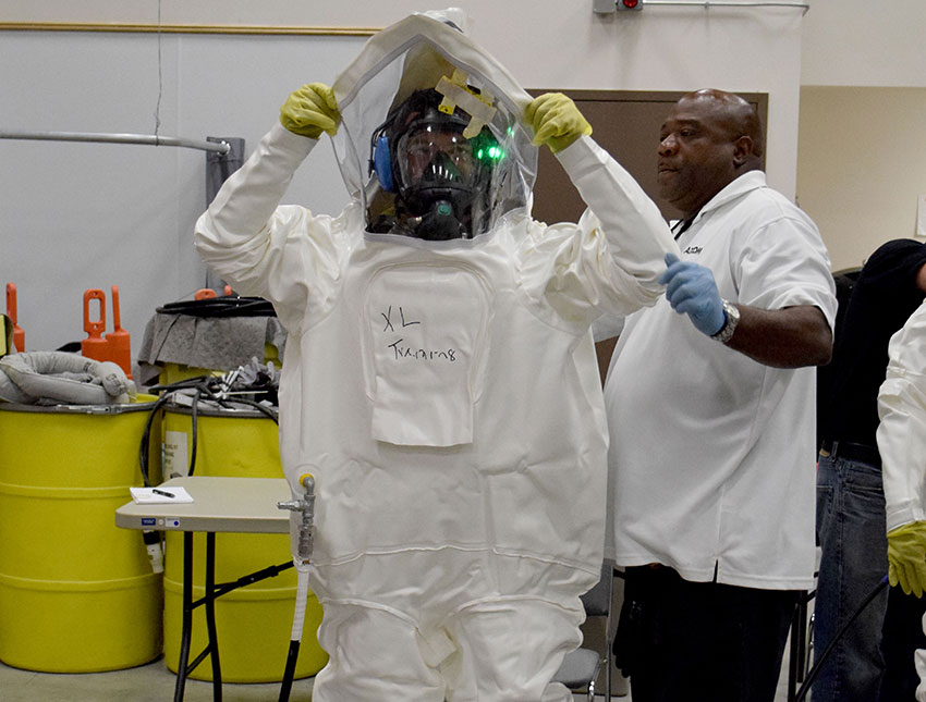 A Blue Grass Chemical Agent-Destruction Pilot Plant munitions handler tries on a Demilitarization Protective Ensemble during a training session. The suit is designed to protect the wearer from chemical agent exposure.