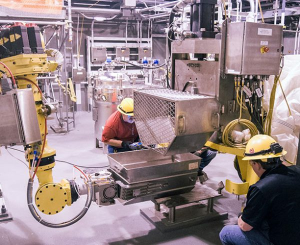 A Blue Grass Chemical Agent-Destruction Pilot Plant startup team member and a contractor test a robot as it moves a hopper in the Explosive Containment Room. The plant has 59 independent systems that must be integrated and tested during the systemization phase.
