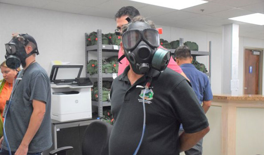 A technician poses for a photo during M40 protective mask fitting at the Blue Grass Chemical Agent-Destruction Pilot Plant. During operations, workers will be required to wear slung masks and don them in the unlikely event of a chemical-agent release.