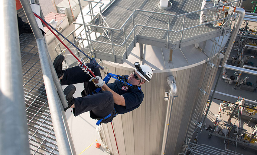 A Blue Grass Army Depot firefighter rappels down the side of a Blue Grass Chemical Agent-Destruction Pilot Plant storage tank as part of a quarterly training activity.