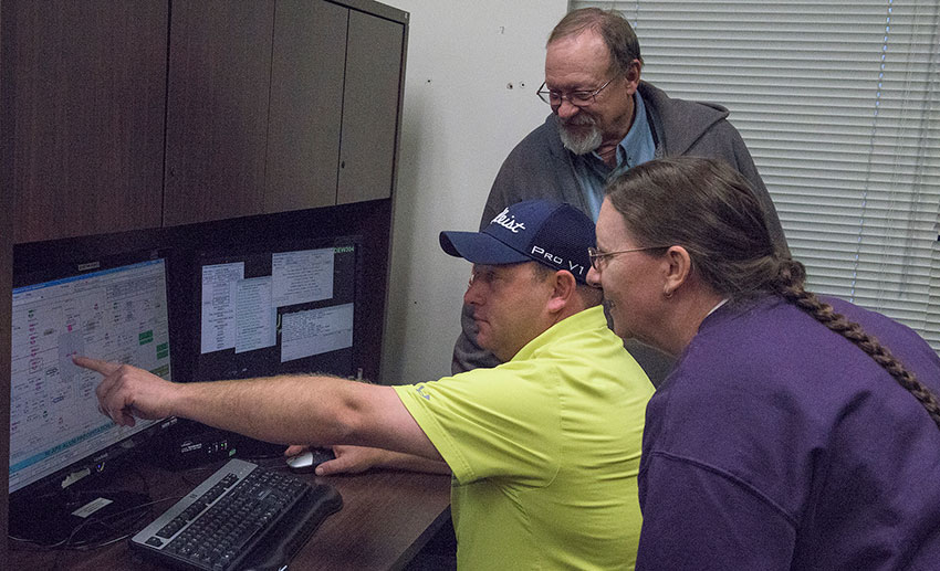 A multi-departmental team of Blue Grass Chemical Agent-Destruction Pilot Plant technicians discusses programming the simulator that will be used to train Control Room operators.