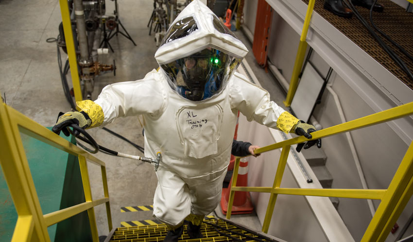 A maintenance worker in a protective suit climbs the stairs in a simulated work environment during a training session.