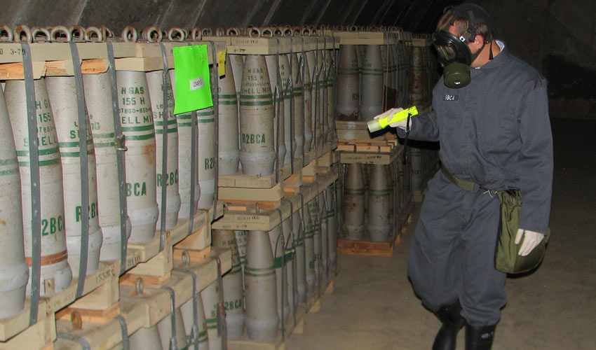 A Blue Grass Chemical Activity technician inspects projectiles stored at the Blue Grass Army Depot. To be able to work with the chemical materials, this worker was vetted through the U.S. Army's Chemical Personnel Reliability Program.