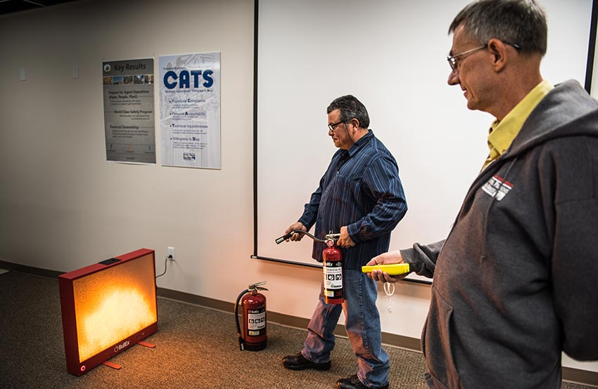 A Blue Grass Chemical Agent-Destruction Pilot Plant trainee attempts to put out a simulated fire with a laser-equipped extinguisher while a training specialist remotely controls the situation