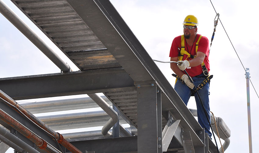 A Blue Grass Chemical Agent-Destruction Pilot Plant worker demonstrates proper use of a Horizontal Life Line as he pulls cable on a pipe rack during the plant's construction phase. The HLLs are designed to prevent falls from heights.