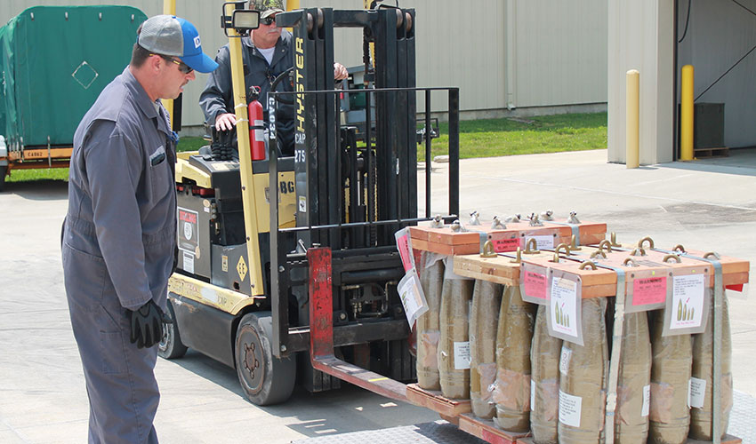 A Blue Grass Chemical Activity (BGCA) worker observes as another worker practices loading dummy munitions onto a metal tray for placement in a secure transport container May 25. BGCA workers recently began a comprehensive munitions handling training program to ready them for operations.