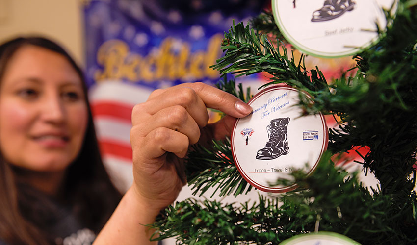 A Blue Grass Chemical Agent-Destruction Pilot Plant employee chooses an ornament with a wish-list item written on it from the Soldier's Angels tree. Chosen items were collected and donated to benefit deployed troops and veterans.