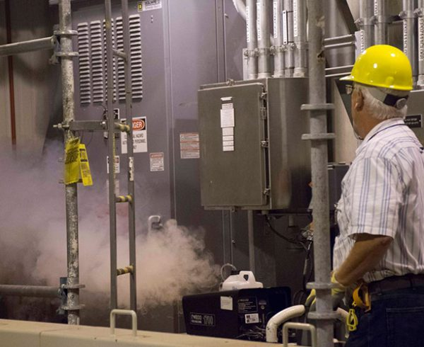 A technician performs a smoke test in the Munitions Demilitarization Building at the Blue Grass Chemical Agent-Destruction Pilot Plant. This test allowed workers to find and seal air leaks within the building before performing a system demonstration procedure on the ventilation system.