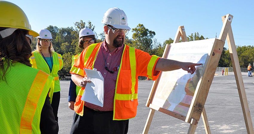 Jeff Brubaker, site project manager, points out features on the Explosive Destruction Technology facility site map to members of a process review team. Workers in the background are surveying the site for the munitions destruction facility that began construction at the Blue Grass plant in 2014.