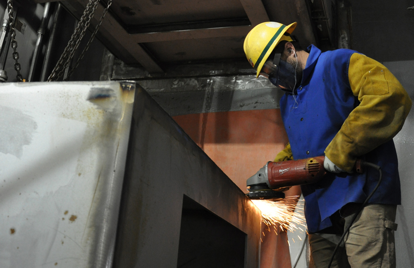A Blue Grass worker grinds the edge of a plenum, a pressurized steel housing that acts as a transition point between Munitions Demilitarization Building blast valves and ductwork. An installed plenum can be seen above his head.