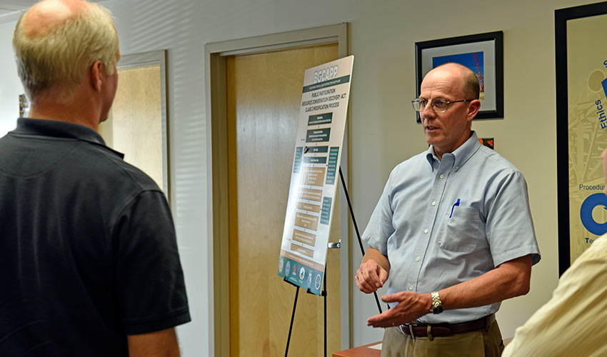 Wade Hollinger, deputy site project manager, Blue Grass Chemical Agent-Destruction Pilot Plant, explains the public participation process to an attendee at a July 19 permit modification public meeting.