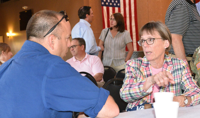 ACWA Program Executive Officer Suzanne Milchling speaks with Nathan Whittington, Emergency Management Program Specialist, Colorado Division of Homeland Security and Emergency Management, at a June 27, 2018 public meeting about chemical weapons destruction in Pueblo, Colorado.