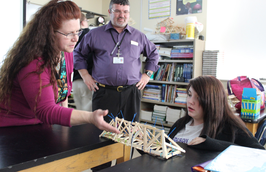 Engineer Sandra Davis, quality specialist, helps an eighth-grade student understand the principles of engineering by building a bridge made from Popsicle sticks during Engineers Week in February 2015.