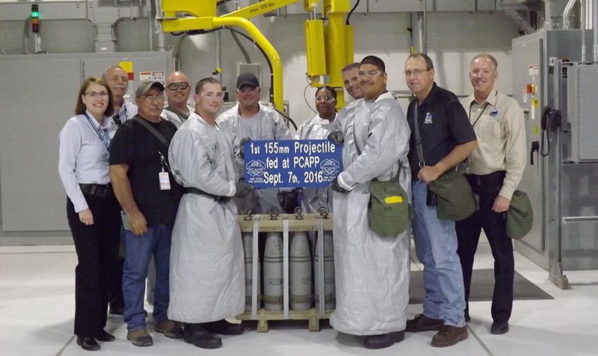 Pueblo Chemical Agent-Destruction Pilot Plant ordnance technicians and project leadership pose for a picture just before the first munition was processed through the plant. The pilot testing phase of operations began on Sept. 7.