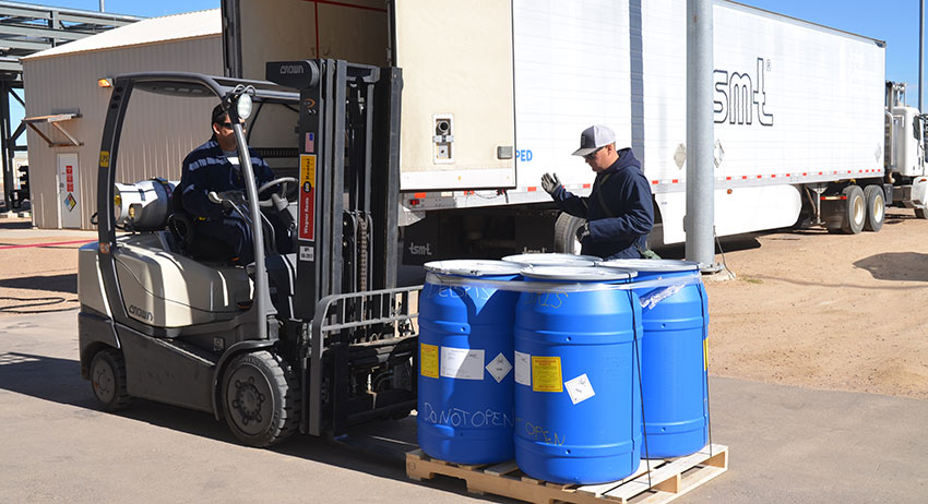 Workers move a pallet of polyurethane drums containing contaminated waste greater than one Vapor Screening Level. The waste was trucked to Port Arthur, Texas, for incineration.