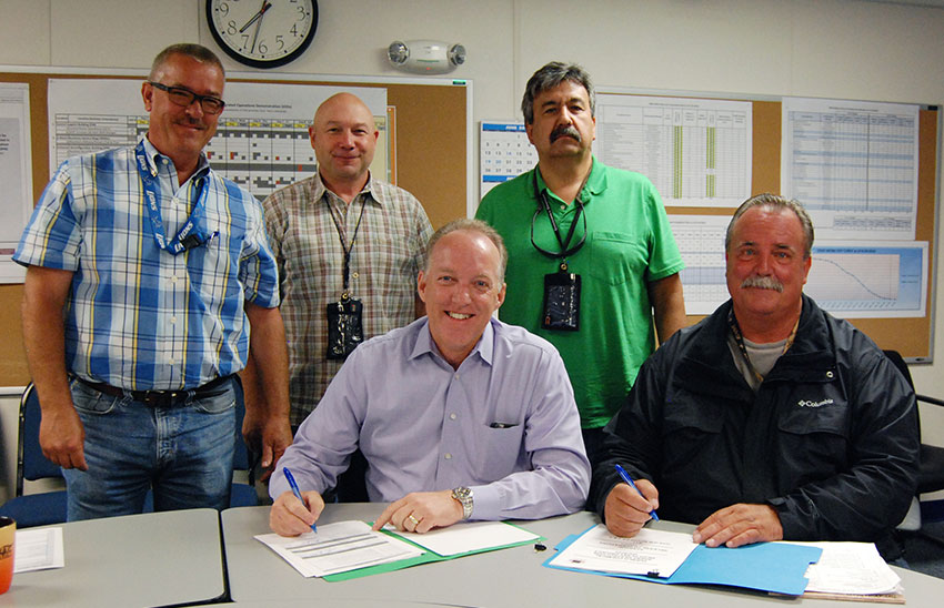 Plant managers pose for a photo while certifying systems turned over to operations. The last of Pueblo Chemical Agent-Destruction Pilot Plant systems have been turned over, signifying people, paper and plant are coming together to ready for pilot testing, the phase before operations.