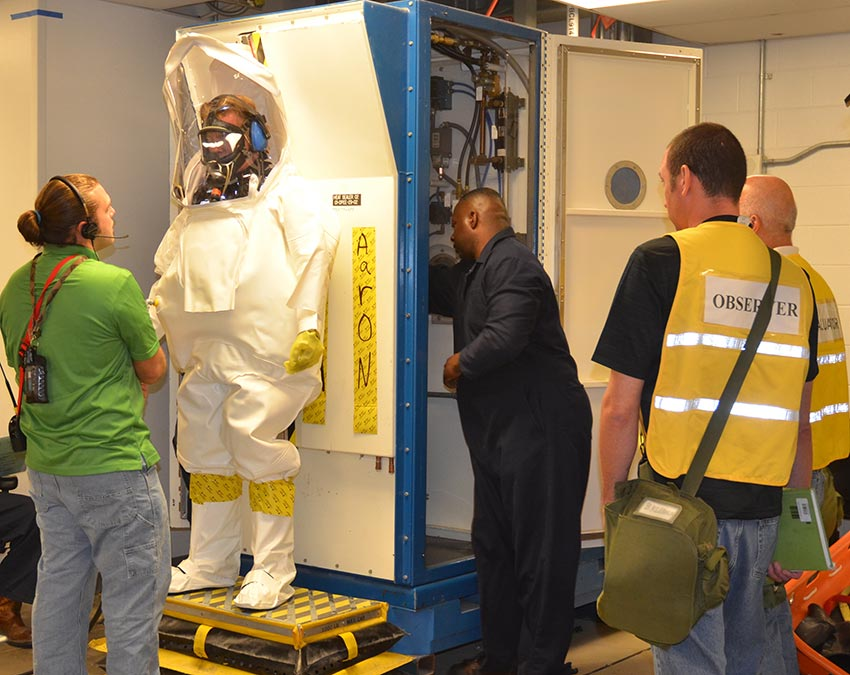 Representatives from regulatory agencies observe as a Pueblo Chemical Agent-Destruction Pilot Plant technician gets sealed into the Demilitarization Protective Ensemble. The evaluations certify the plant, paper and people are ready to start processing mustard agent.
