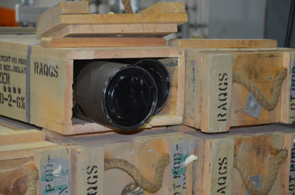 A boxed 105mm projectile awaits reconfiguration, which consists of removing the munition from its wooden box and fiberboard tube.