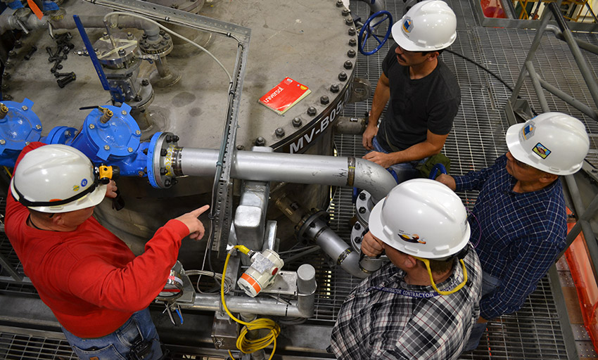 Workers examine a Spent Decon Holding Tank in the Agent Processing Building. Pueblo plant employees are in the process of turning over 63 systems and facilities in preparation for operations.