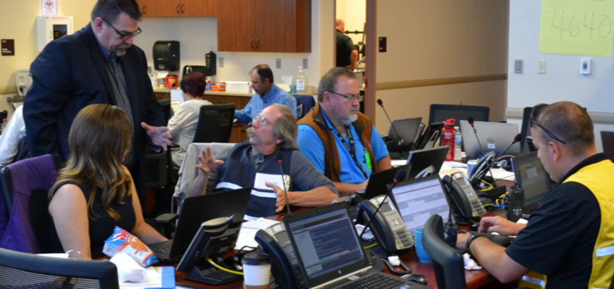 Emergency managers and planners update the state field manager in the Pueblo County Emergency Operations Center.