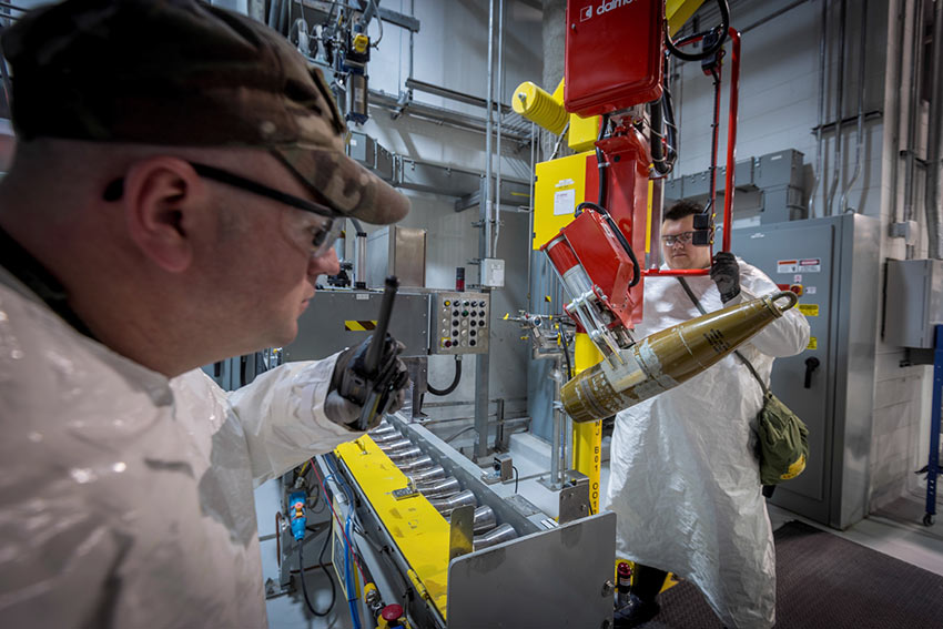 During training exercises, a worker uses a lift assist to place a simulated munition on a conveyor in the Pueblo Chemical Agent-Destruction Pilot Plant's Enhanced Reconfiguration Building. This is an example of the first block in a system designed to align plant readiness activities with permit requirements.