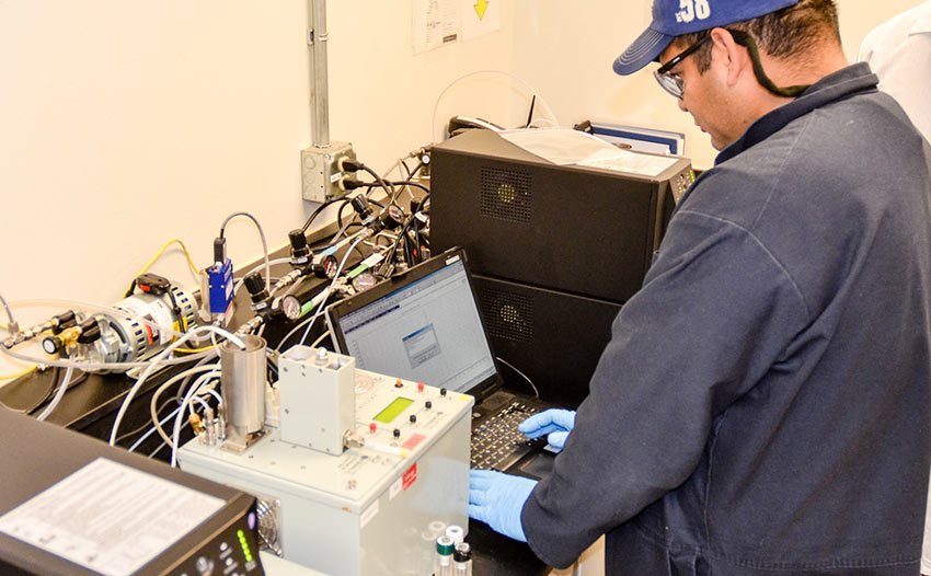 A monitoring technician performs a calibration verification of the Miniature Continuous Air Monitoring System at the Pueblo plant. Recently, the Laboratory has been working to reduce the likelihood of false-positive or false-negative alarms.