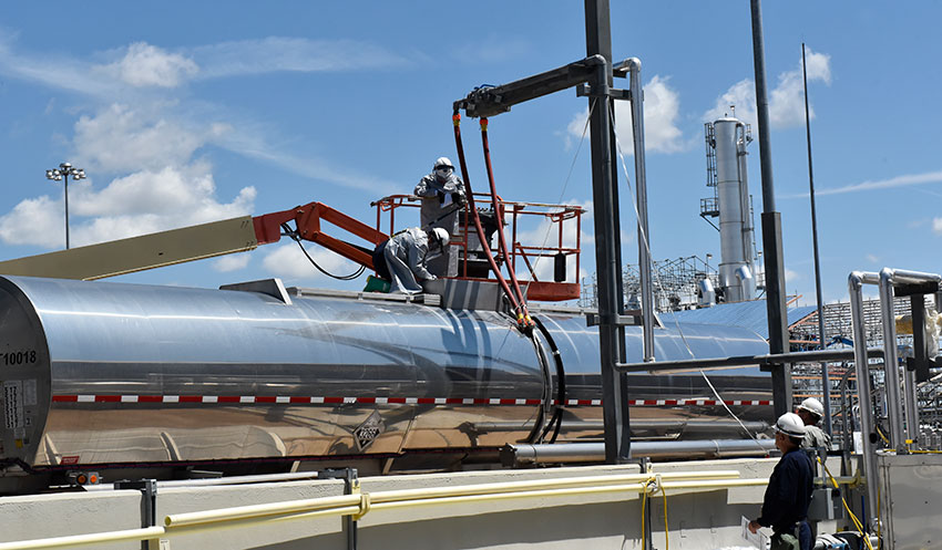 Plant operators connect a hose to a tanker to begin the process of transferring wastewater from a 30-day Hydrolysate Storage Tank.