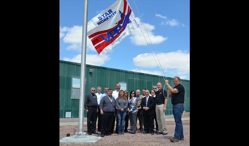 In April 2015, members of the Pueblo Chemical Agent-Destruction Pilot Plant Voluntary Protection Programs steering committee gathered in front of the Personnel Support Building with Brad Baptiste, regional VPP manager, fifth from right, to pose with the flag awarded by the Occupational Safety and Health Administration.