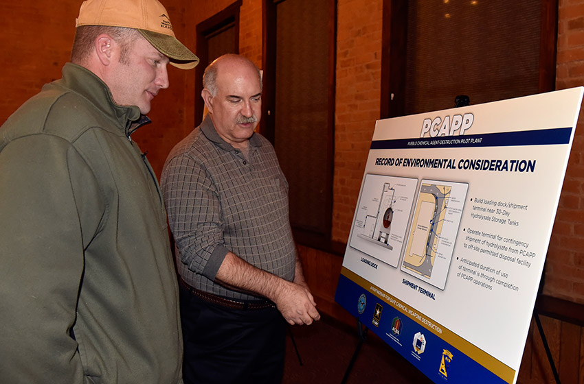 Deputy Site Project Manager Walton Levi discusses the Record of Environmental (REC) Consideration with Luke Armstrong, sergeant, Colorado State Patrol, during the REC poster session held on Jan. 25.