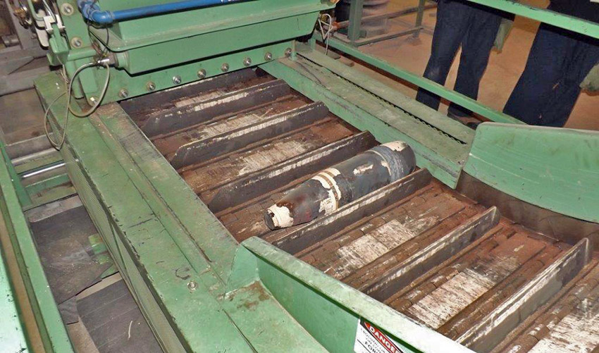 A munition, used in high heel testing, sits on the Munition Treatment Unit discharge conveyor. Its paint was cooked off, down to metal, which is not typical for normal processing and is indicative of heel being present in the munition.