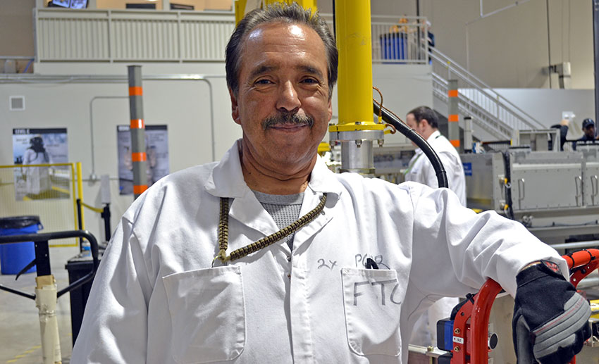 Johnny Lujan, ordnance technician, stands in front of a lift assist, a piece of equipment he routinely uses, at the Pueblo Chemical Agent-Destruction Pilot Plant Training Facility. He has been employed at the plant, in different capacities, since 2008.