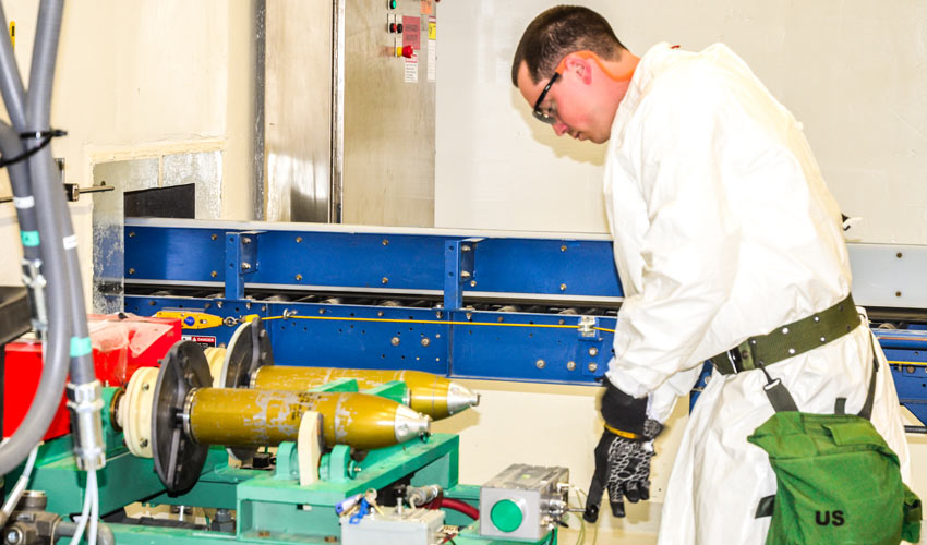 A Pueblo Chemical Agent-Destruction Pilot Plant ordnance technician removes the rear assembly of a 4.2-inch simulated mortar round with the twin spindle removal machine.