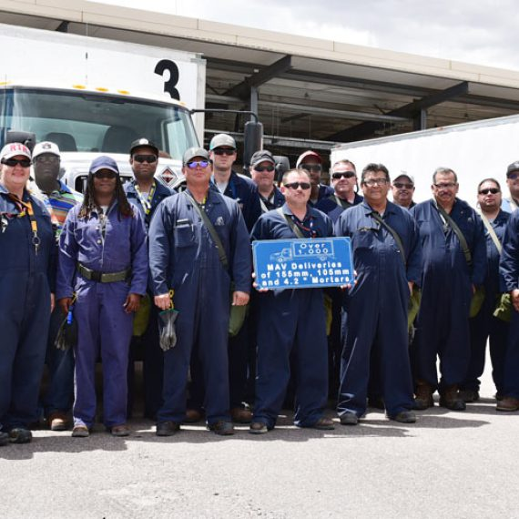 Pueblo Chemical Agent-Destruction Pilot Plant munition transporters stand in front of Modified Ammunition Vehicles to commemorate their 1,000th delivery of munitions from storage igloos to the plant.