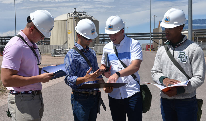 Engineering students, from left, Nick Z., Adam C., Parker I., and Jonah T., review site plans as part of their many duties as Pueblo Chemical Agent-Destruction Pilot Plant interns.