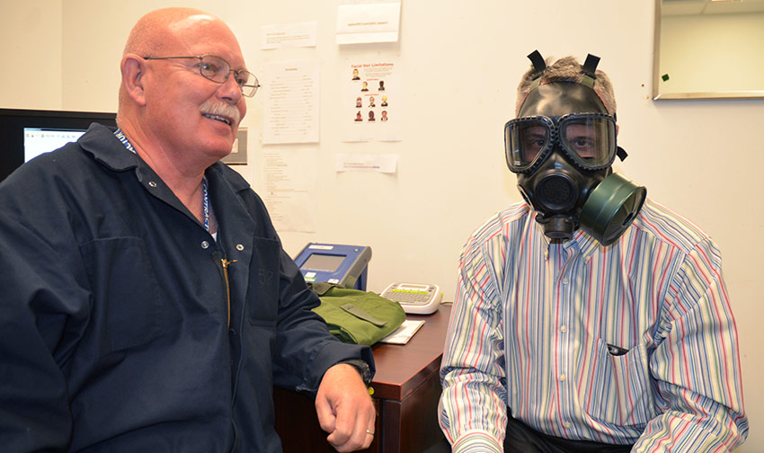 Rick Holmes, Bechtel Pueblo Team project manager, looks at the camera just after being fitted for a protective mask by Jeff Hotchkiss, personal protective equipment technician.