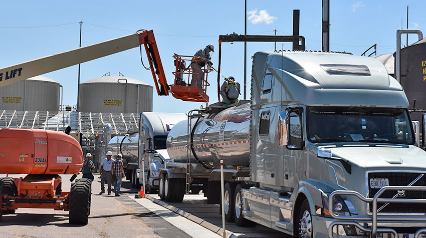 A boom lifts a plant operator onto a tanker to assist in transferring wastewater from a 30-day Hydrolysate Storage Tank into the tanker for transport from the Pueblo Chemical Agent-Destruction Pilot Plant to Veolia Environmental Services Hazardous Waste Incinerator, Port Arthur, Texas.