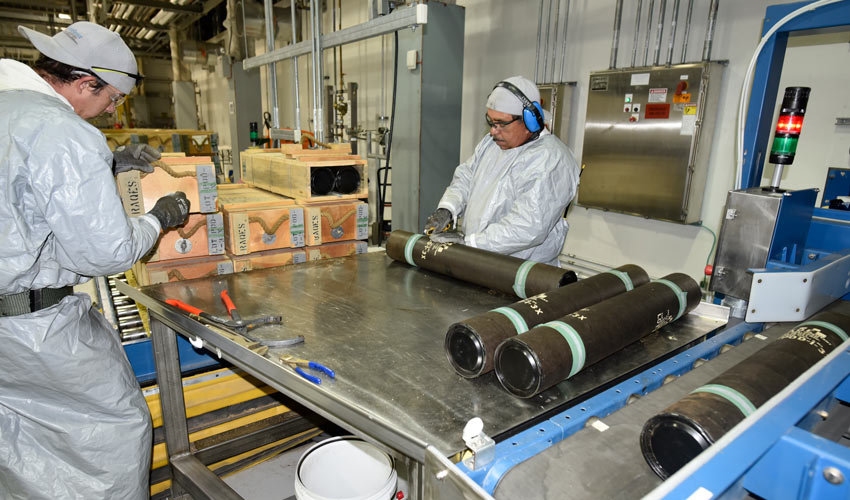 Pueblo Chemical Agent-Destruction Pilot Plant ordnance technicians work to remove 105mm projectiles from wooden boxes and fiberboard tubes.