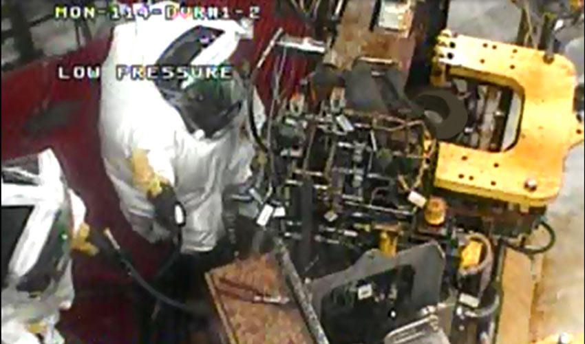 Maintenance workers make a toxic area entry in Demilitarization Protective Ensemble to work on the Munitions Washout System. (Photo from closed-circuit video.)