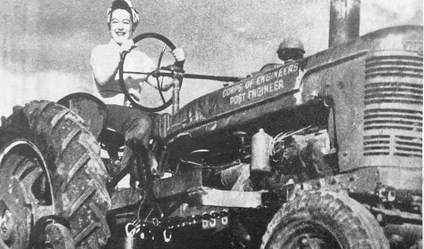 "A photograph from U.S. Army Pueblo Chemical Depot archives shows a ""lady soldier,"" employed during World War II, picking up scrap with a magnetized bar underneath the tractor."
