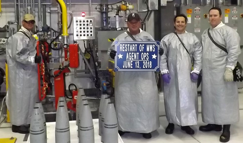 Ordnance technicians stand next to a pallet of reconfigured 155mm projectiles to commemorate the restart of agent operations at the Pueblo Chemical Agent-Destruction Pilot Plant June 13.